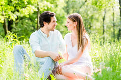Couple in grass on meadow looking at each other Stock Photo