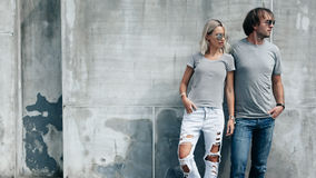 Couple in gray t-shirt over street wall. Two hipster models men and women wearing blank gray t-shirt, jeans and sunglasses posing against rough concrete wall in stock photos