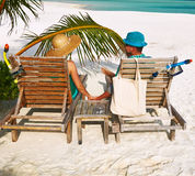 Couple in green on a beach at Maldives. Couple in green on a tropical beach at Maldives royalty free stock images