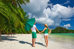 Couple in green on a beach at Seychelles Stock Photography
