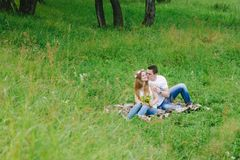 Couple in a forest area cuddling a plaid lovely royalty free stock photo