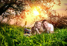 Couple on green grass. Young beautiful couple lying on blanket around green grass and pointing at the camera. Sunset sky background stock photos