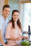Couple with green salad in the kitchen Royalty Free Stock Photos