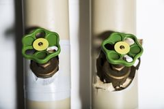 Couple of green valves on metallic pipes stock photography