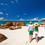 Couple in green walking on a beach at Seychelles Stock Photo