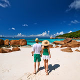 Couple in green walking on a beach at Seychelles Stock Images