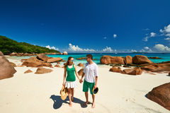 Couple in green walking on a beach at Seychelles Stock Photography