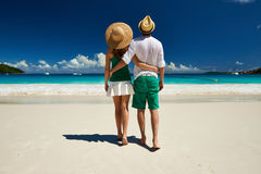 Couple in green walking on a beach at Seychelles Stock Photos