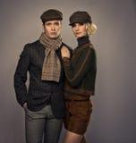 Couple on grey background. Elegant couple in caps isolated on grey background stock photo