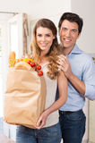 Couple With Grocery Bag In Kitchen Royalty Free Stock Photography