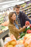 Couple in grocery store buying vegetables stock photography