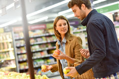 Couple at grocery store choosing fruits Stock Photo