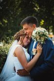 Couple groom and bride hugging and kissing on nature park background Royalty Free Stock Photography
