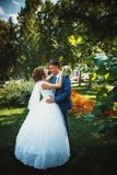 Couple groom and bride hugging and kissing on nature park background Stock Photos