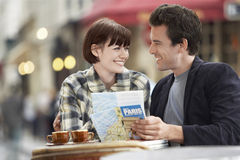 Couple With Guidebook At Outdoor Cafe Royalty Free Stock Photography