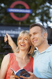 Couple With Guidebook Outdoors Stock Image