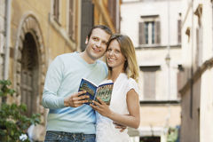 Couple With Guidebook In Rome. Young couple holding guidebook on street in Rome; Italy royalty free stock image