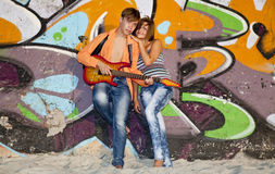Couple with guitar near graffiti wall. Royalty Free Stock Photos