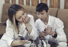 Couple from guy and girl have a tea time in the cafe and looking on the smartphone absorbedly Royalty Free Stock Image