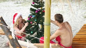 Couple guy and girl in santa hat greeted the new year and Christmas on the beach. To decorate a Christmas tree on a stock video footage