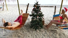 Couple guy and girl in santa hat greeted the new year and Christmas on the beach. To decorate a Christmas tree on a stock video