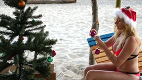 Couple guy and girl in santa hat greeted the new year and Christmas on the beach. To decorate a Christmas tree on a stock footage