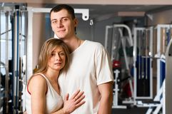 Couple in gym. Young couple is standing and embracing in gym Royalty Free Stock Photo
