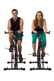 Couple at the Gym. Attractive Couple on exercise bikes smiling. Isolated against a gray studio background. Vertically framed shot Royalty Free Stock Photo
