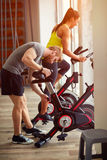 Couple in gym exercise on sport bicycle Royalty Free Stock Photography
