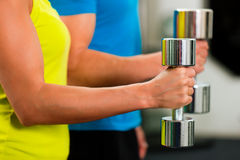 Couple in gym exercising with dumbbells Royalty Free Stock Photo
