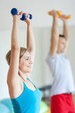Couple in gym exercising with dumbbells Stock Photo