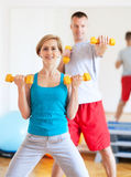 Couple in gym exercising with dumbbells Royalty Free Stock Image