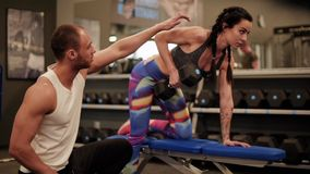 Couple on the gym. Man guiding woman lifiting weights stock footage
