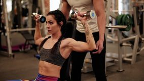 Couple on the gym. Trainer assisting while woman lifting stock video