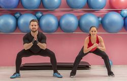 Couple in the Gym. Young couple doing stretching exercises in a gym Stock Photos