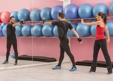 Couple in the Gym. Young couple doing stretching exercises in a gym Royalty Free Stock Photos
