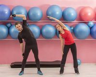 Couple in the Gym. Young couple doing stretching exercises in a gym Stock Images