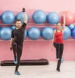Couple in the Gym. Young couple doing stretching exercises in a gym Stock Photo