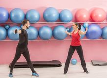 Couple in the Gym. Young couple doing stretching exercises in a gym Royalty Free Stock Images