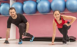 Couple in the Gym. Young couple doing stretching exercises in a gym Stock Photography