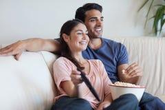 Couple hållande ögonen på TVstunder som äter popcorn Royaltyfri Foto