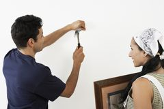 Couple Hammering Nail Into Wall stock photos