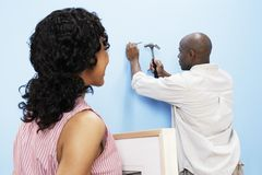 Couple Hammering Nail Into Wall Royalty Free Stock Photography