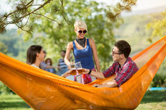 Couple in hammock in nature toast with glasses of beer with fema Royalty Free Stock Images