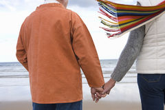 Couple hand in hand on beach, mid section, rear view Stock Images
