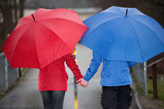 Couple hand in hand  walk in the rain with umbrella Stock Images