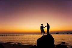 Couple hand in hand watching sunrise and sunset. Stock Photos