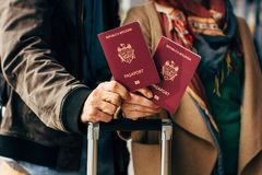 Couple Hand holding Passport . Traveler with Luggage Travel concept. People tourism. Biometric Moldavian passports. Hand holding Passport Traveler with Luggage Royalty Free Stock Photos