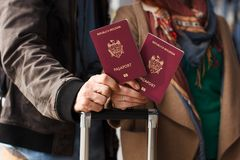 Couple Hand holding Passport . Traveler with Luggage Travel concept. People tourism. Biometric Moldavian passports. Hand holding Passport Traveler with Luggage Royalty Free Stock Image