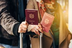 Couple Hand holding Passport . Traveler with Luggage Travel concept. People tourism. Biometric Moldavian passports. Hand holding Passport Traveler with Luggage Royalty Free Stock Photo
